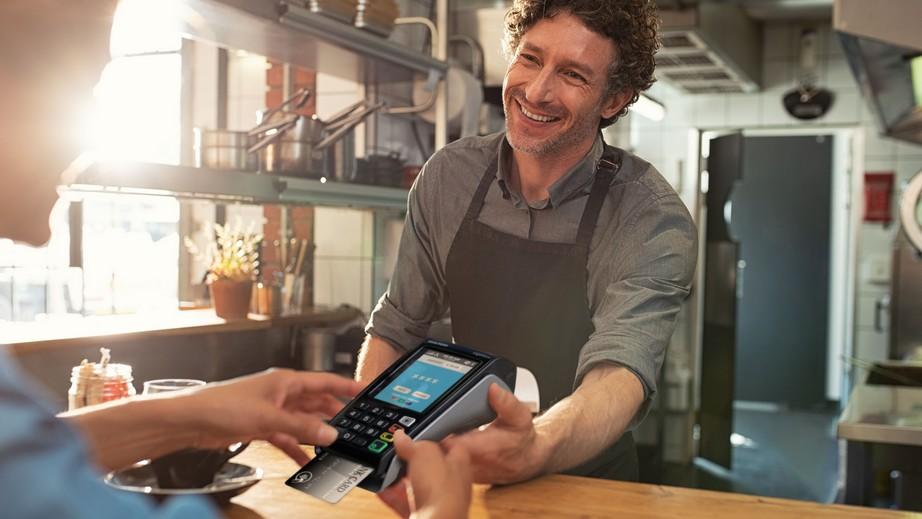 Mężczyzna płacący w walucie karty przez terminal eService