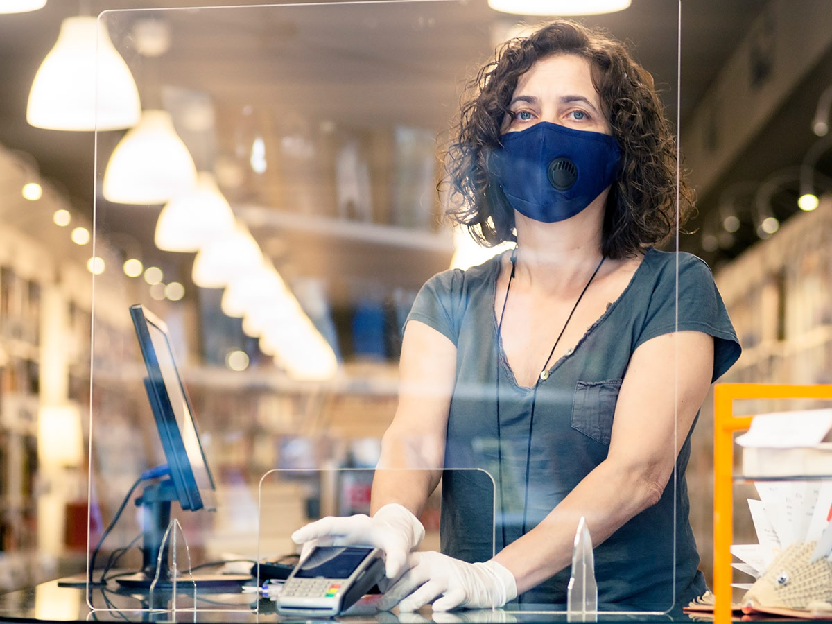 A woman in a mask and protective gloves holding the terminal